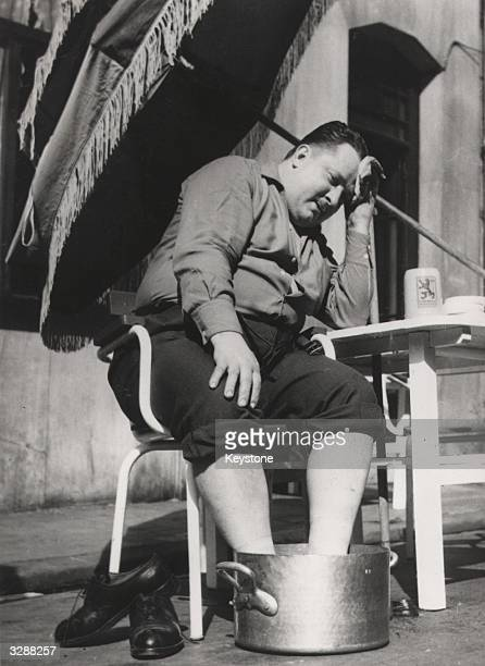 A Parisian relaxes in the heat outside a cafe his feet soaking in a pan of water