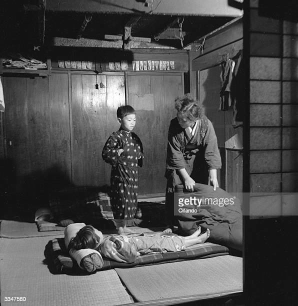 A small boy and his sister prepare for their night's sleep in a rural Japanese village