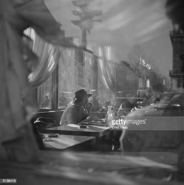 A woman drinking at a table in a Paris cafe
