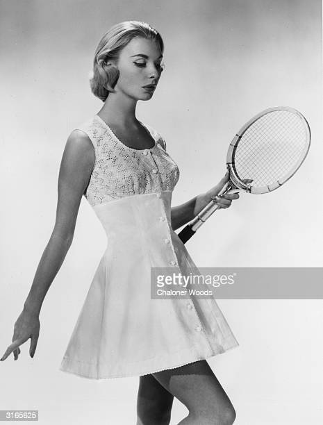 A woman modelling a short white tennis dress with buttons down the front and a lace bodice