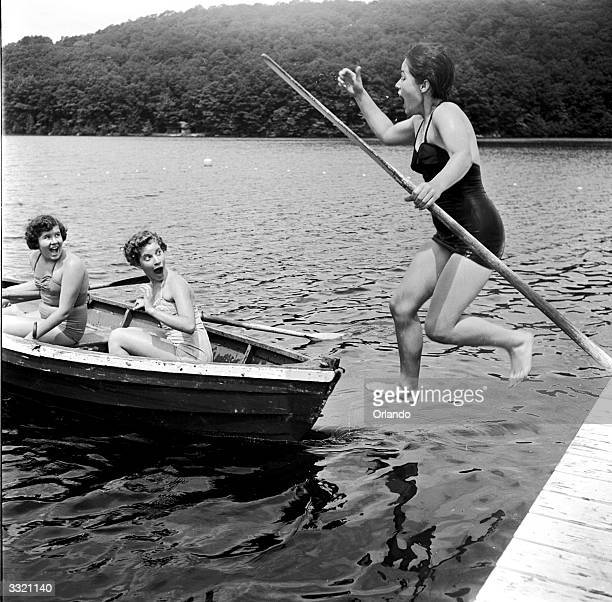 A young woman jumping in to a lake narrowly avoiding a rowing boat containing startled friends