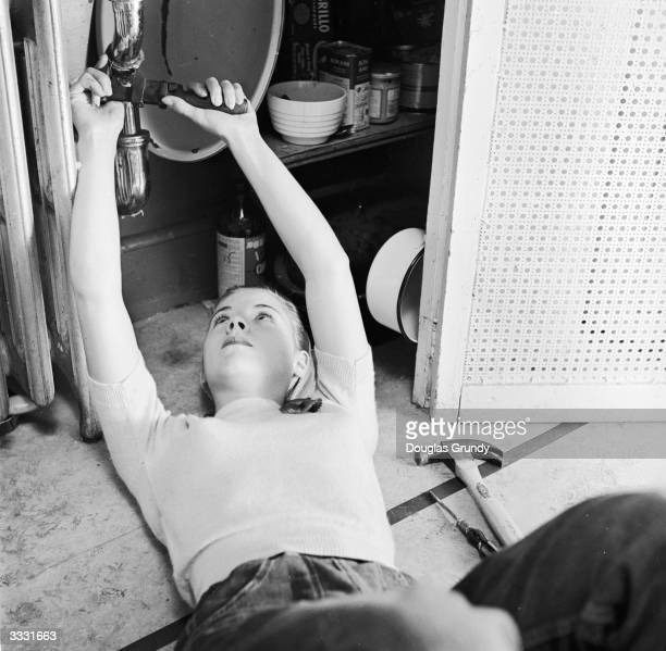 American housewife Vicky Buchanan of Floral Park Long Island does the plumbing when her husband is away on active duty