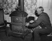 An elderly American gentleman getting his old fashioned 'shunck' stove burning