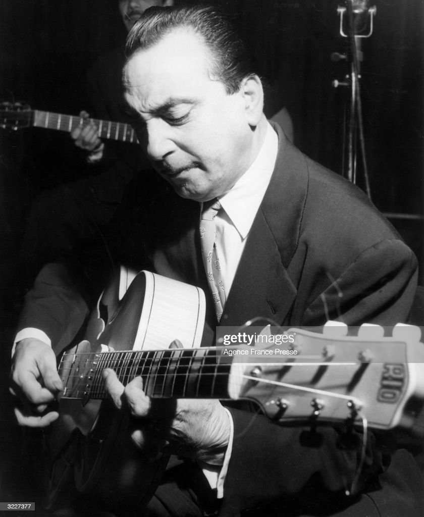 Belgian-born jazz guitarist <a gi-track='captionPersonalityLinkClicked' href=/galleries/search?phrase=Django+Reinhardt&family=editorial&specificpeople=1567148 ng-click='$event.stopPropagation()'>Django Reinhardt</a> (Jean Baptiste Reinhardt, 1910 - 1953), performs on stage,. He squints as he sits and plays his guitar.