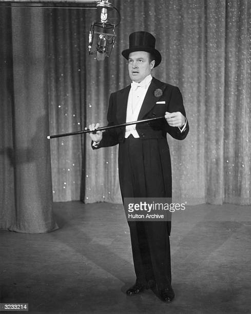 Britishborn entertainer Bob Hope holding a cane and singing into a microphone during a rehearsal for the Colgate Comedy Hour television show He is...