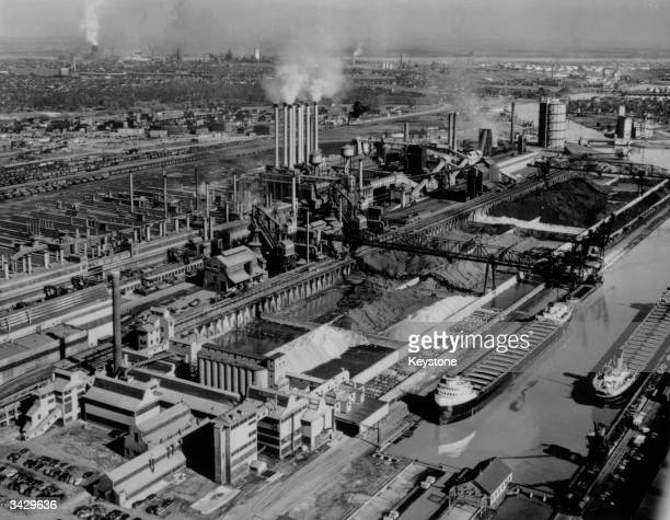 Chimneys belch smoke above the Rouge plant of the Ford Motor Company Dearborn Michigan Cargo ships lie in the dock adjoining the plant