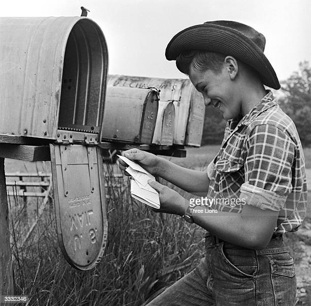 Farm boy Ted Cone reading a letter at the mailbox half a mile from the farm where he lives and works He collects the mail every day