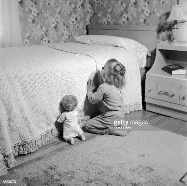 Kneeling by her bed a little girl says her prayers her doll propped up beside her