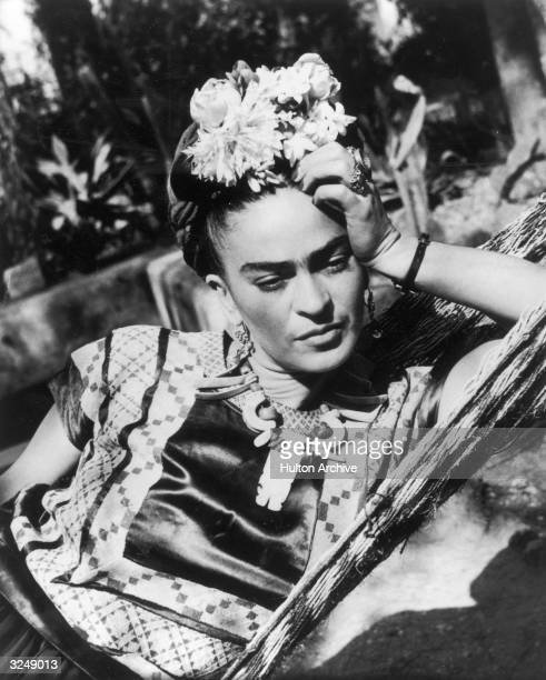 Mexican artist Frida Kahlo wearing a folk costume and flowers in her hair leans her head on her hand while lying in a hammock