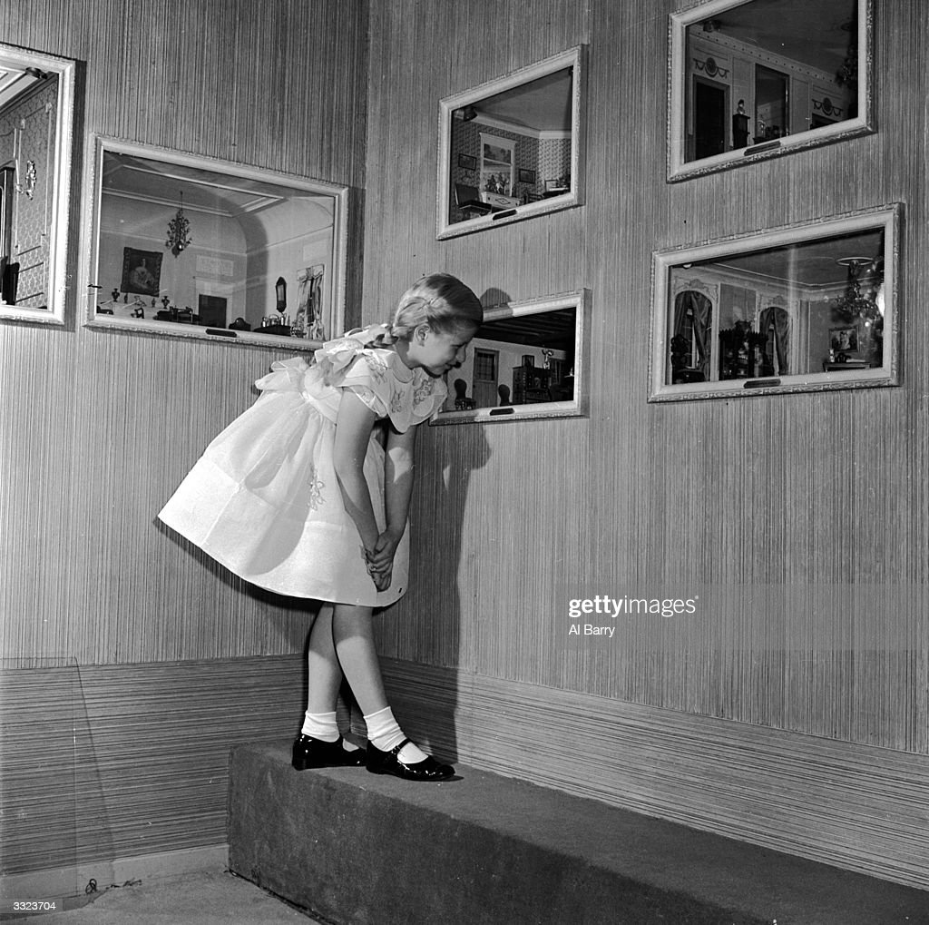 Miniature rooms belonging to the Helena Rubinstein collection being examined by a small girl.