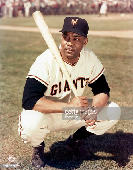 Outfielder Monte Irvin of the New York Giants poses for a portrait crouching and holding a baseball bat 1950s Irvin played for the Giants from...