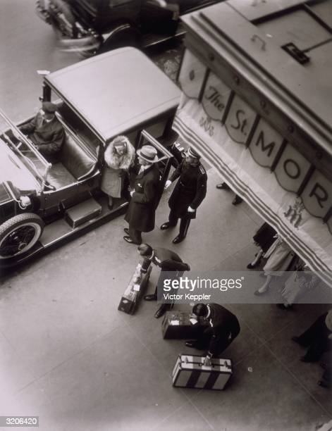 Overhead view of a wealthy couple arriving at the St Moritz Hotel possibly New York City The man in a long coat helps a woman in a coat with fur trim...