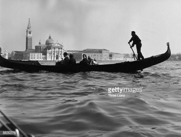 Passengers on a gondola travelling down the Grand Canal which winds through the whole of Venice In the background is the Church of St Georgio