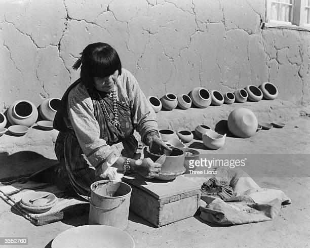 Potter Maria Martinez smooths the sides of another clay pot in her outdoor factory known to Native Americans as Pueblo in San Ildefonso New Mexico