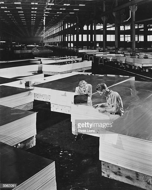 Sheets of aluminium are checked and stacked for shipping after being rolled and polished at a large aluminium mill
