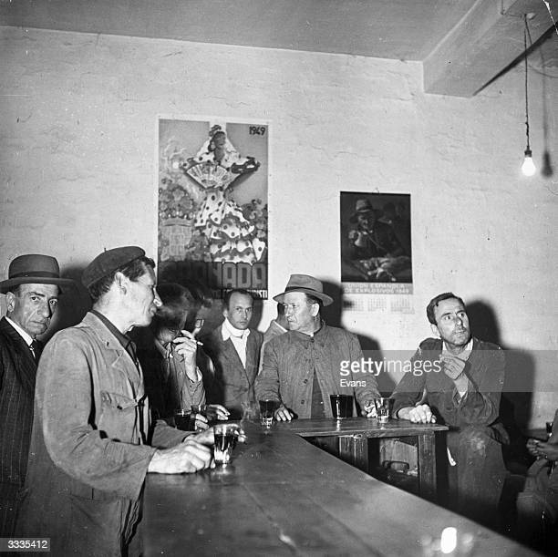 Spanish workers drinking red wine in their local bar