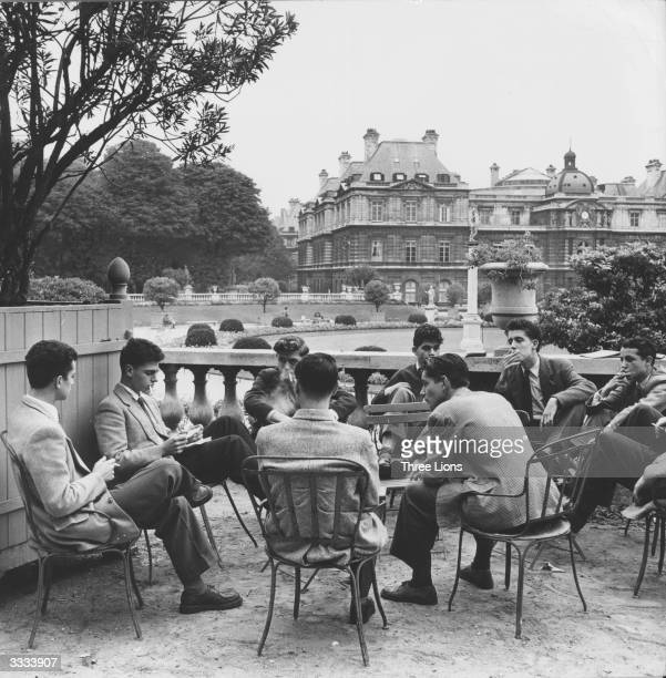 Students from the Sorbonne sit around a table in the Jardin du Luxembourg Paris smoking and relaxing In the background is the Senate building