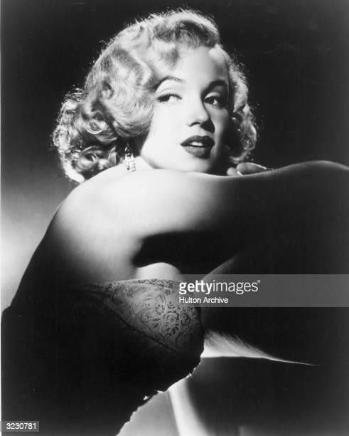 Studio portrait of American actor Marilyn Monroe wearing a strapless dress under a spotlight