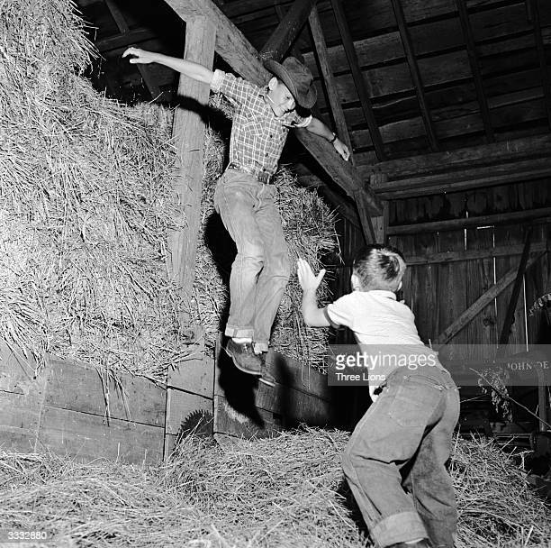 Teenage farm boy Ted Cone and his younger brother Dwight playing in the hayloft of a farm in Connecticut USA