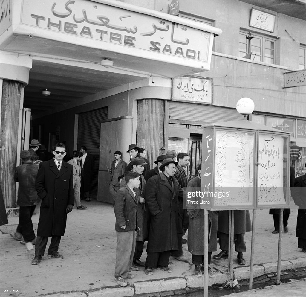 The exterior of Tehran's Theatre Saadi where a group of people study a billboard.