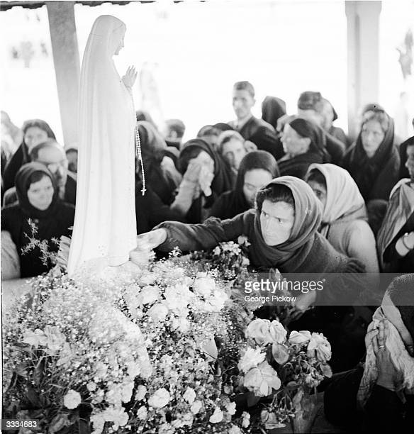 The statue of the Virgin of Fatima is bedecked with flowers at the top of the steps of the Basilica at Fatima Portugal in preparation for its...