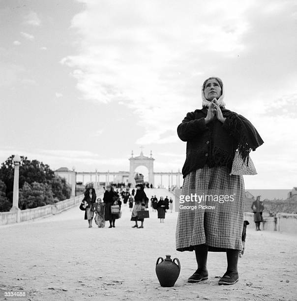 Through the arch leading to the Basilica at Fatima in Portugal a pilgrim with her own jug of water to be blessed makes her devotions Behind another...