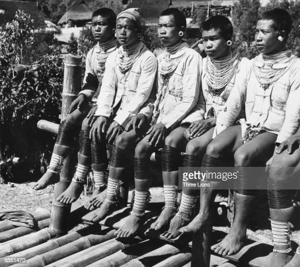 Tribesmen in Burma wearing jewellery and leg bindings typical of the area