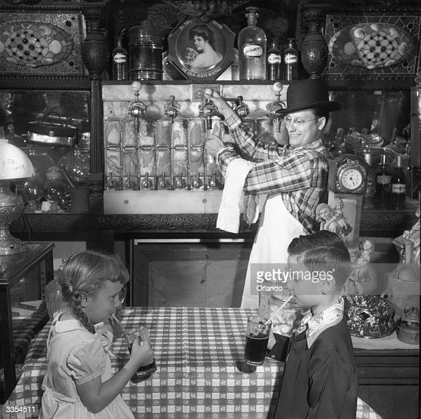 Two children drinking root beer in Wilfred Allen's county store in Sudbury Massachusetts It was the first soda fountain installed in New England in...