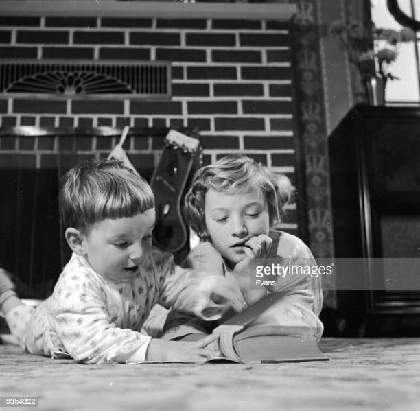 Two children enjoy playing at reading before their bedtime story