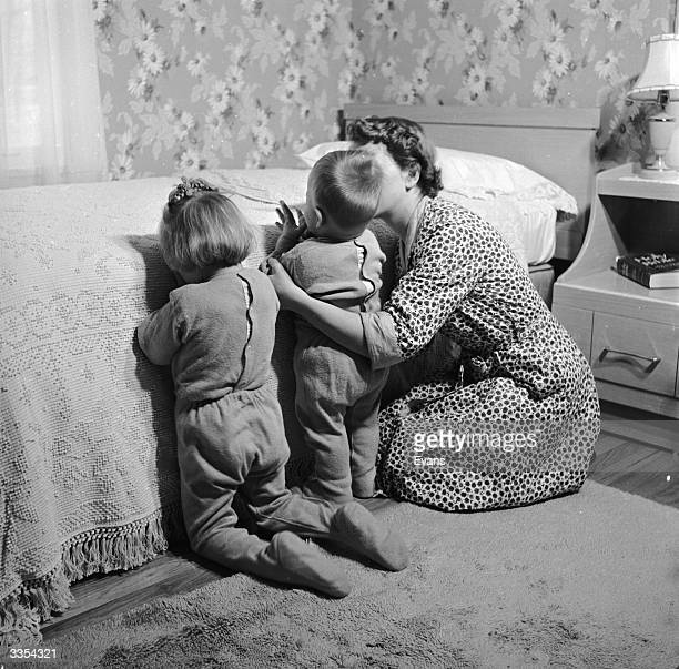 Two children in their pyjamas kneel by a bed to say their prayers helped by mother