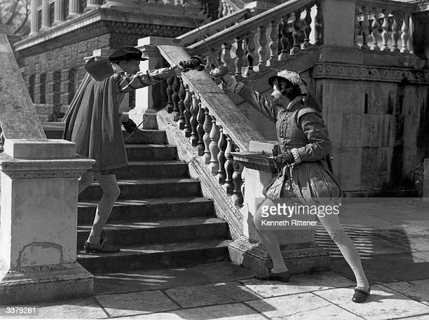 Two gentlemen in Shakespearian costume duelling each armed with an epee and a dagger as they ascend the stairs during battle