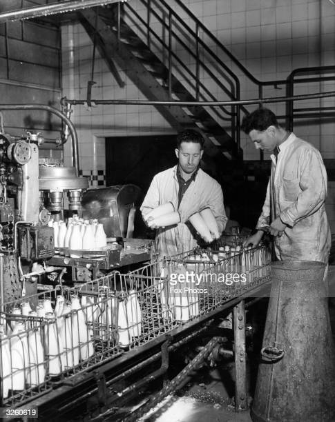 Two men load bottles of milk into crates for distribution at a milk factory in London