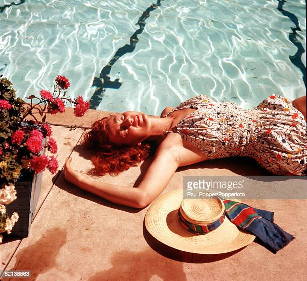 Circa 1950's A woman is pictured sunbathing by a swimming pool