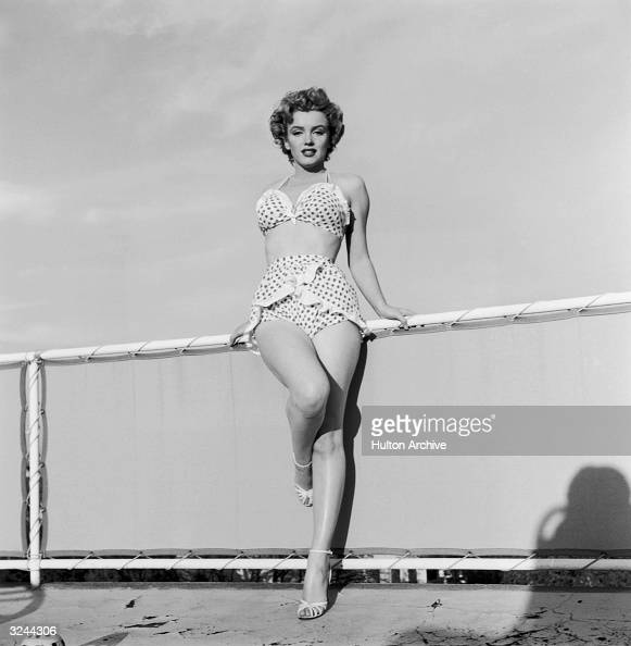 EXCLUSIVE Fulllength portrait of American actor Marilyn Monroe standing in a twopiece polka dot bathing suit and heels