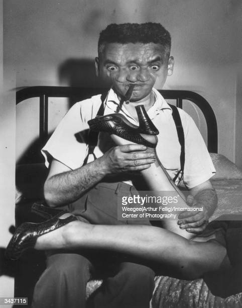Polishborn American photographer Arthur 'Weegee' Fellig poses as a lecherous talent scout inspecting a young lady's shoe for his 1953 publication...