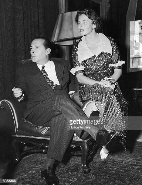 Swedishborn actor Ingrid Bergman holding a cigarette sits on the edge of a chair with her husband Italian film director Roberto Rossellini at their...