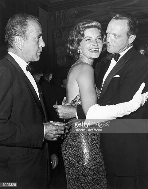 American actors Lauren Bacall and Van Heflin dance at a formal party while Bacall's husband American actor Humphrey Bogart looks on early 1950s Both...