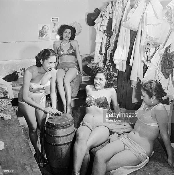 Bikiniclad chorus girls in a burlesque show relax backstage by beating out a rythm on a native drum at the Tivoli Theatre Mexico City