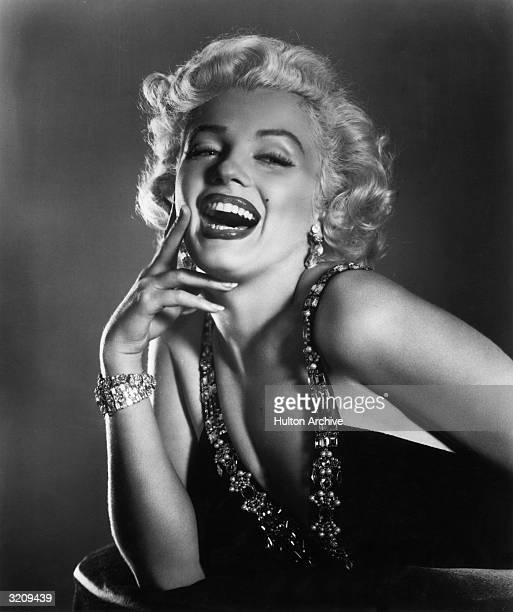 Halflength portrait of American actor Marilyn Monroe laughing her hand raised to her cheek wearing a low cut dress trimmed in jewels