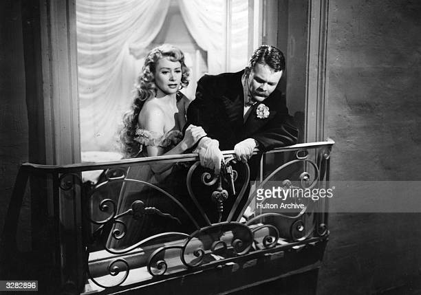 Martine Carol the French leading lady is holding the arm of a gentleman on the balcony while looking down into the street in a scene from the film...