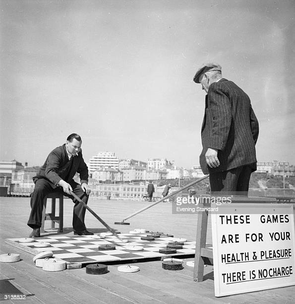 Two men using long poles to position the pieces as they enjoy a free game of deck draughts on the pier at Bournemouth in Dorset