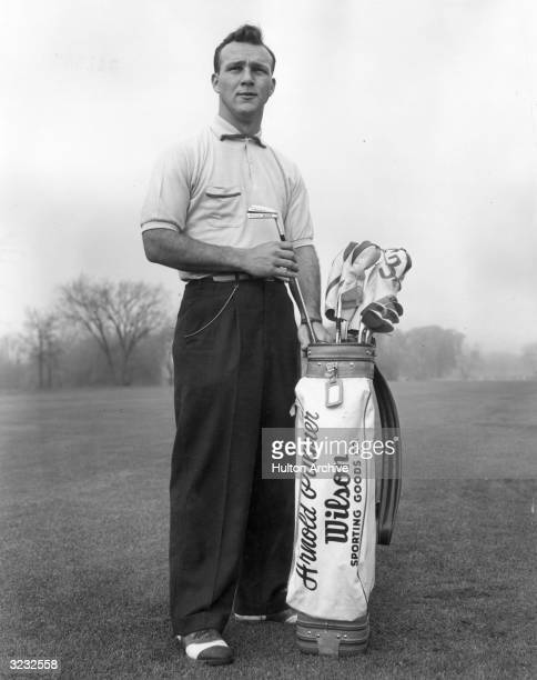 A fulllength portrait of American golfer Arnold Palmer pulling a driving iron from a golf bag on a golf course