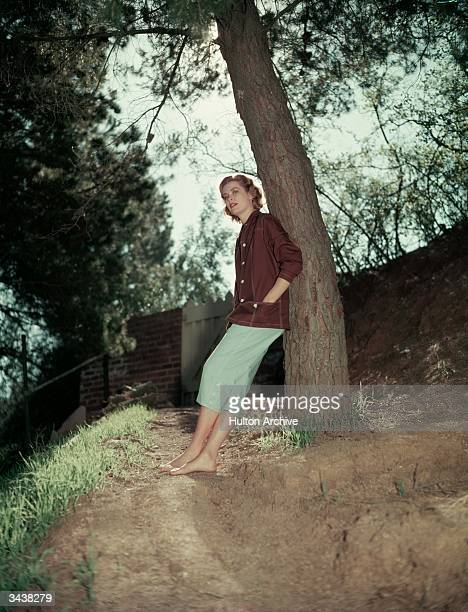 American actor Grace Kelly leaning against a tree barefoot