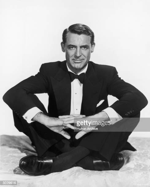 British actor and comedian Cary Grant sits with his legs crossed in a tuxedo in a promotional portrait for director Sidney Sheldon's film 'Dream Wife'