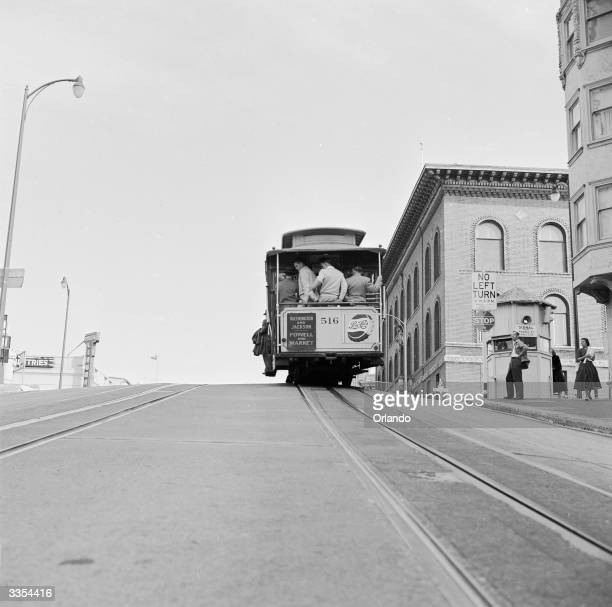 One of San Francisco's famous cable cars arrives at the top of a hill laden with passengers This mode of public transport has been used in the city...