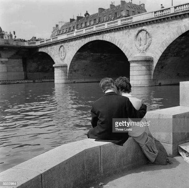 A couple sit for a while by the river Seine in Paris