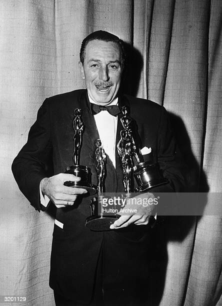 American cartoonist and producer Walt Disney laughs while struggling to hold four Oscar statuettes simultaneously backstage at the Academy Awards Los...
