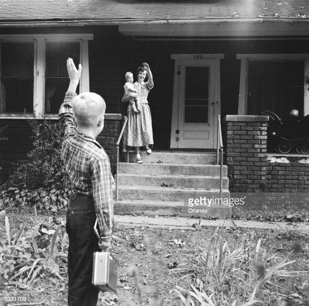 Mrs Walz with infant Billy in her arms waves goodbye to her son Dick as he leaves their New Jersey home for school Mrs Walz still has a busy day...