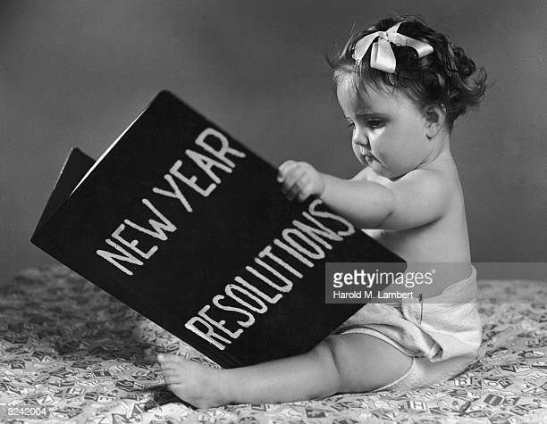 A baby wearing diapers sits and holds a large book of New Year Resolutions