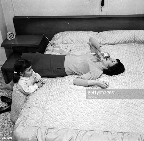 A babysitter is too involved on the telephone to notice that her young charge wants her attention